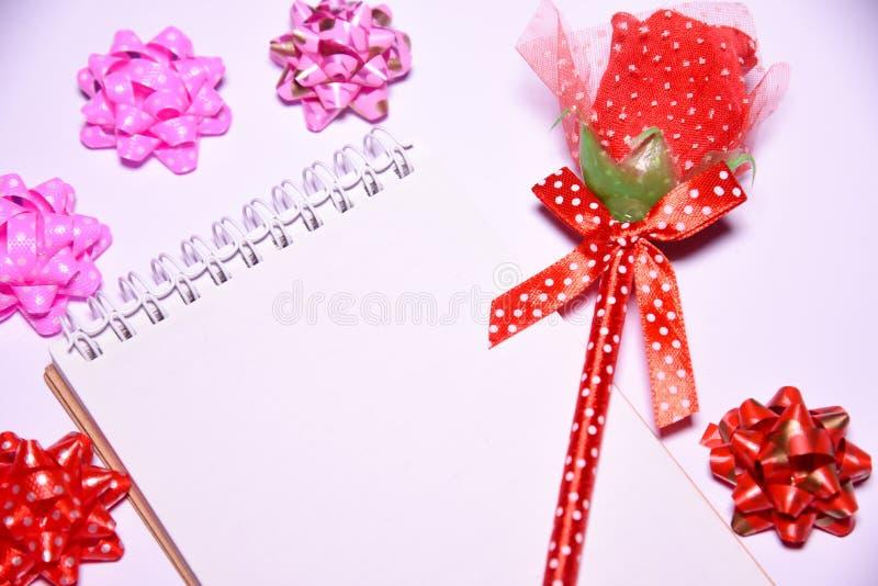Fondo del día de tarjetas del día de San Valentín Rosa roja en la libreta en blanco para los lazos de satén del espacio y de la c imágenes de archivo libres de regalías