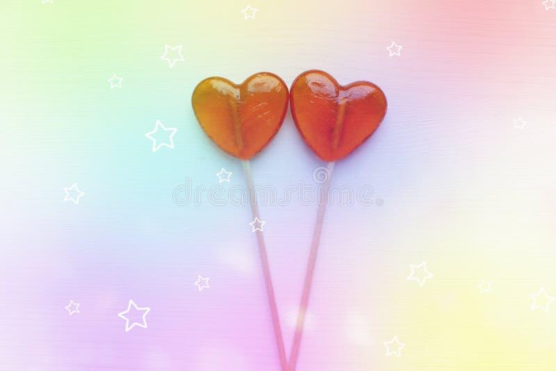 Fondo del día del ` s de la tarjeta del día de San Valentín Dos piruletas en un palillo en forma de corazón aislado en el fondo r fotografía de archivo