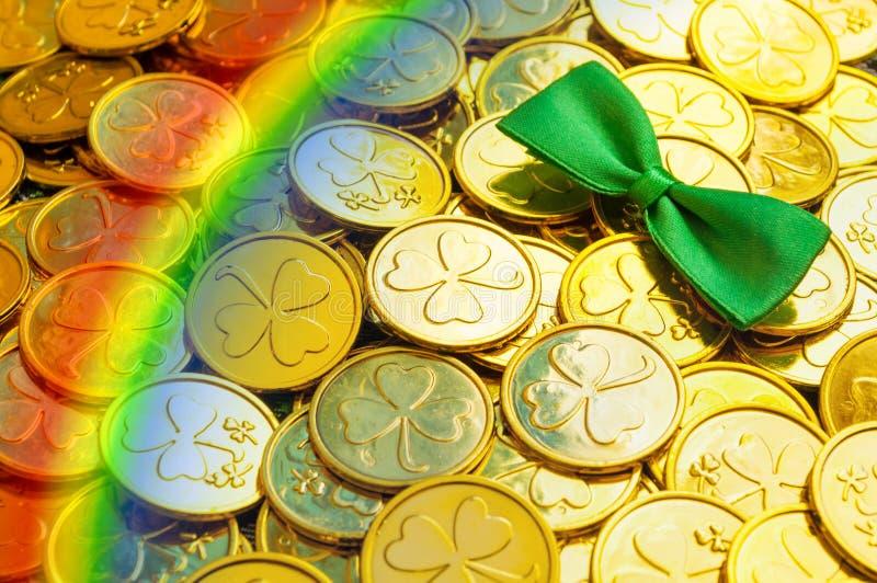 Fondo del día del `s del St Patrick Monedas de oro con el trébol, la corbata de lazo verde y el arco iris, símbolos del día de St fotos de archivo libres de regalías