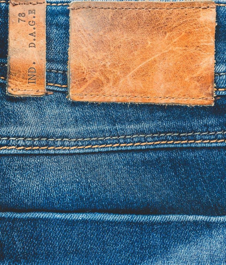 Fondo del denim Le blue jeans con un'etichetta di cuoio marrone svuotano lo spazio immagini stock libere da diritti