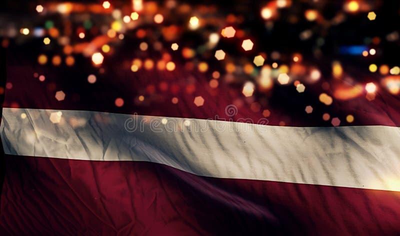 Fondo del extracto de Bokeh de la noche de la luz de la bandera nacional de Letonia imagen de archivo