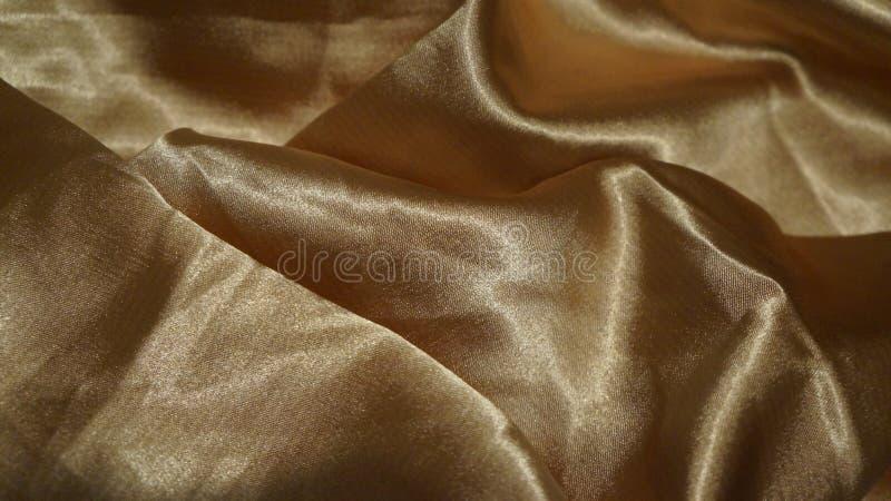 Fondo del extracto del paño del satén del oro imagen de archivo