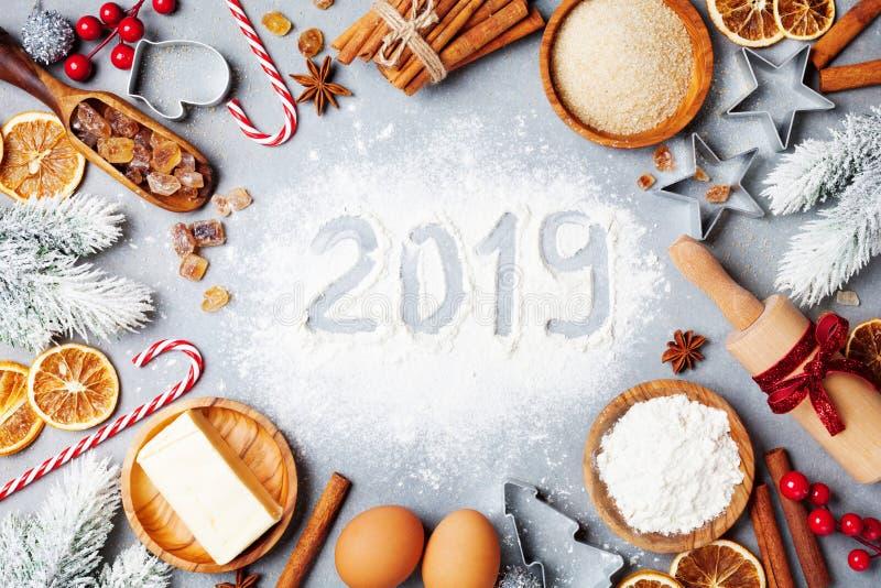 Fondo del forno con gli ingredienti per la cottura decorata con l'albero di abete ed il nuovo anno 2019 Farina, zucchero bruno, u fotografia stock libera da diritti