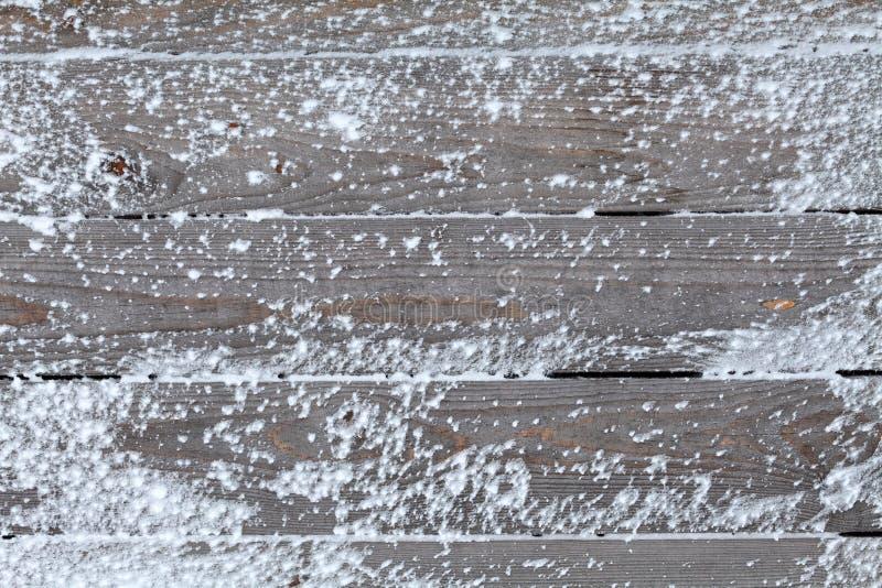 Fondo del invierno con nieve natural en el tablero de madera fotografía de archivo