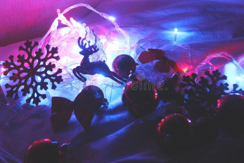Fondo del invierno de la Navidad colorida y del Año Nuevo con la guirnalda adornada de las luces, ciervo el chispear, bolas fotos de archivo libres de regalías