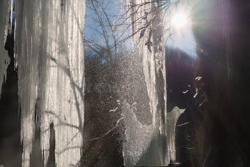 Fondo del invierno, debajo de la cascada congelada contra el sol foto de archivo