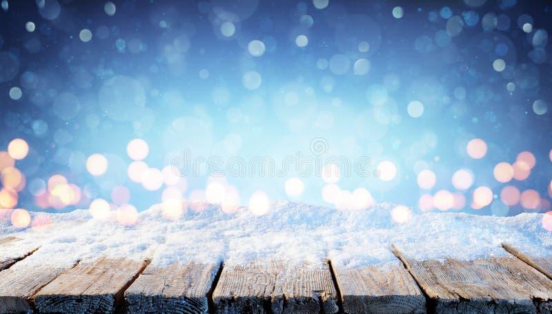 Fondo del invierno - tabla Nevado con las luces de la Navidad fotos de archivo