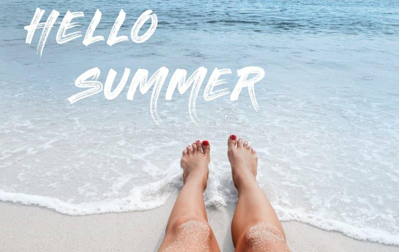 Fondo del mar con verano de las letras hola Piernas femeninas en la playa fotos de archivo