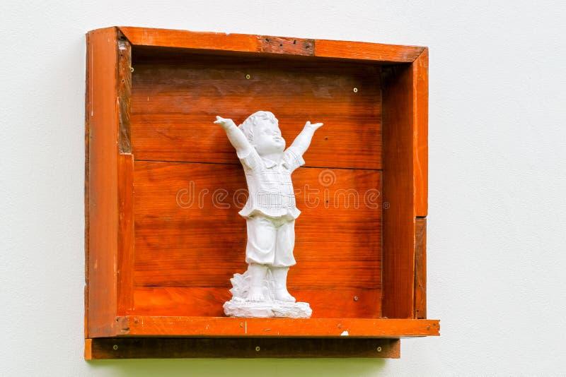 Fondo del muro di cemento con la scatola ed il carrello di legno delle statue fotografia stock