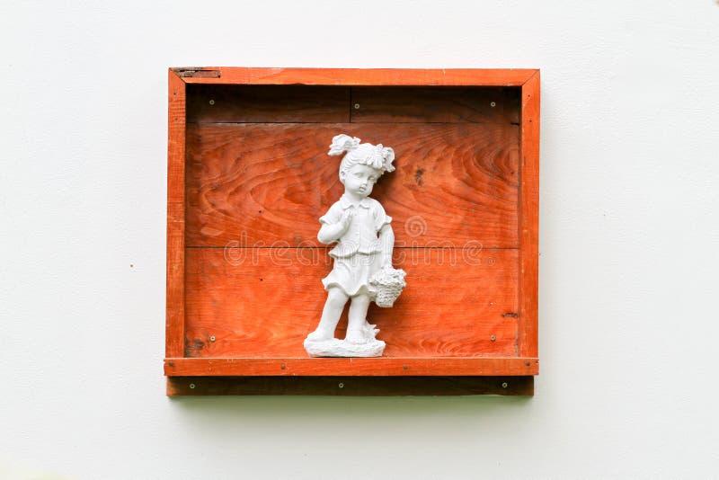 Fondo del muro di cemento con la scatola ed il carrello di legno delle statue immagini stock