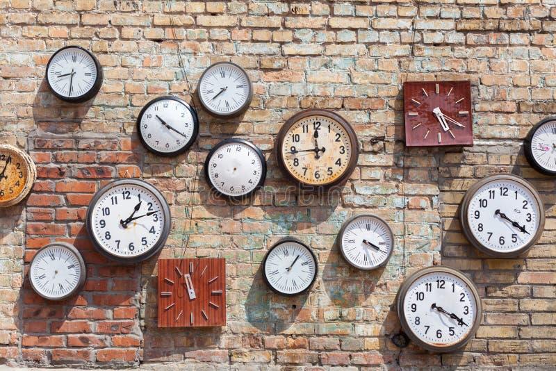 Fondo del muro di mattoni con numeroso in tondo e gli orologi quadrati fotografie stock libere da diritti