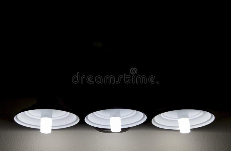 Fondo del negro con el sitio para la copia con el behow de tres lámparas que brilla en una pared áspera del yeso fotos de archivo
