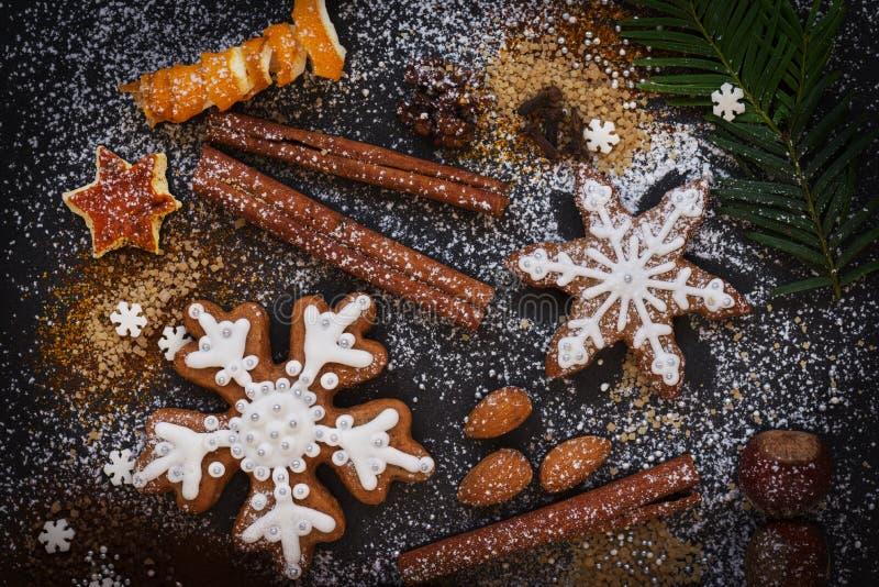 Fondo del nuovo anno o di Natale dei biscotti, delle spezie, dei dadi con zucchero e dei fiocchi di neve del pan di zenzero Vista fotografia stock