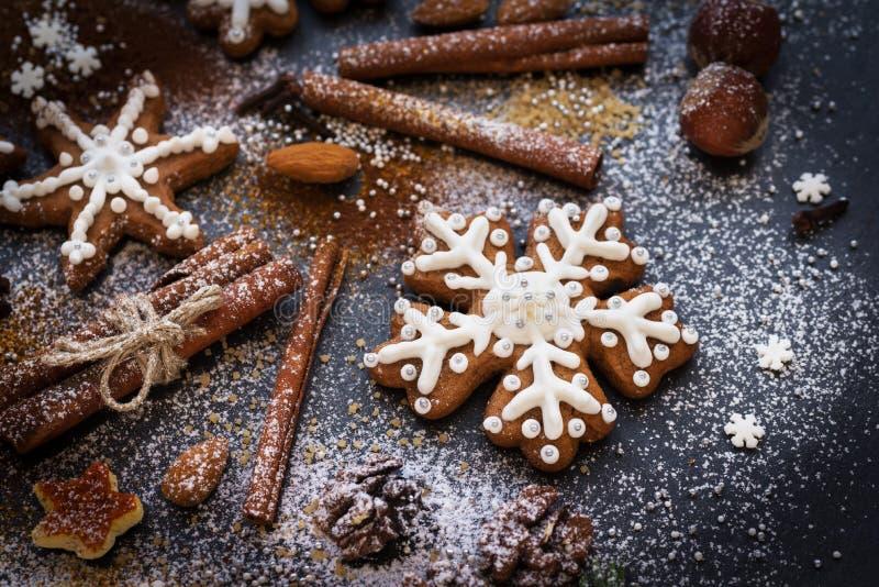 Fondo del nuovo anno o di Natale dei biscotti, delle spezie, dei dadi con zucchero e dei fiocchi di neve del pan di zenzero Vista fotografie stock