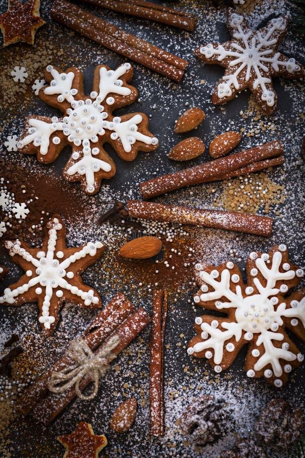 Fondo del nuovo anno o di Natale dei biscotti, delle spezie, dei dadi con zucchero e dei fiocchi di neve del pan di zenzero Vista immagini stock