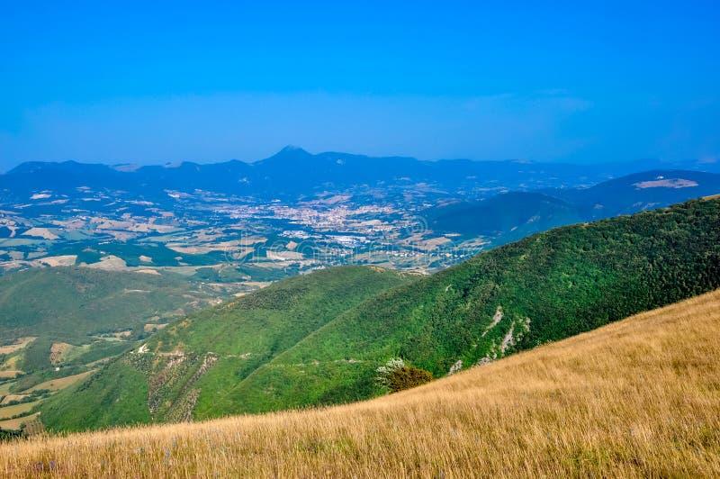 Fondo del paisaje hermoso en campos verdes y cielo azul en Umbría fotos de archivo