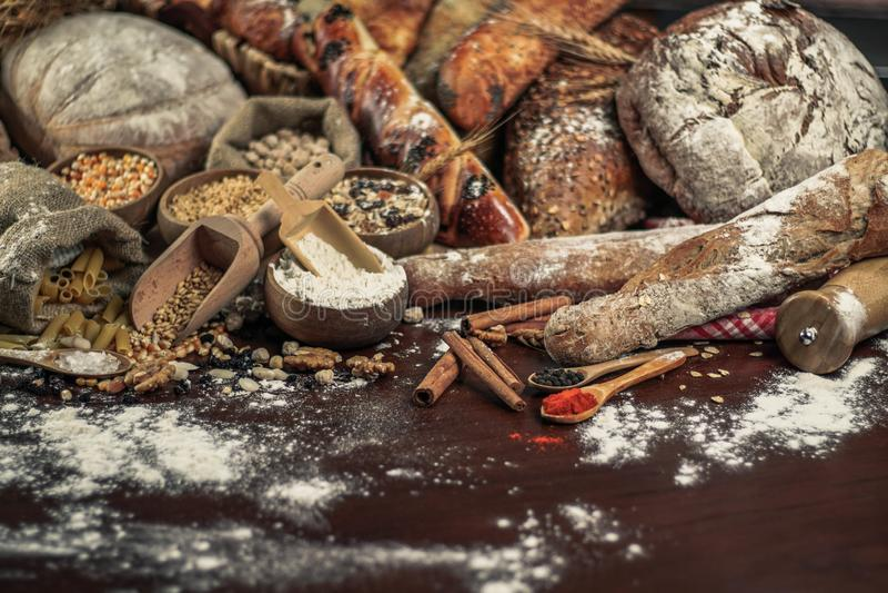 Fondo del pan Brown y panes enteros blancos del grano envueltos en la composición del papel de Kraft en la madera oscura rústica  fotos de archivo libres de regalías