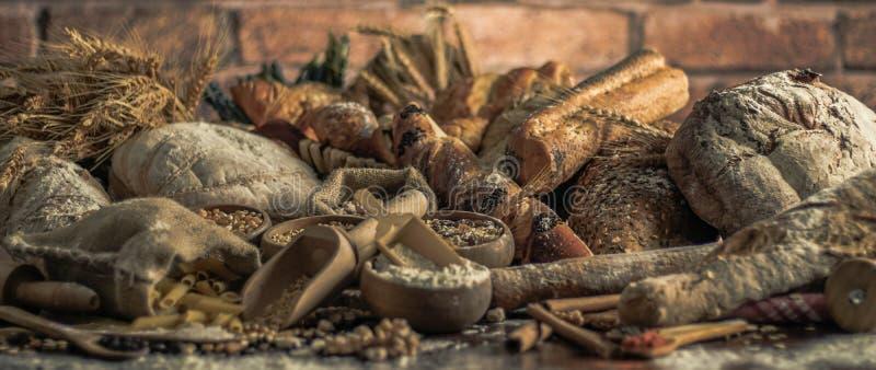 Fondo del pan Brown y panes enteros blancos del grano envueltos en la composición del papel de Kraft en la madera oscura rústica  foto de archivo libre de regalías