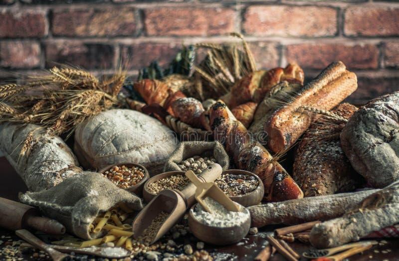 Fondo del pan Brown y panes enteros blancos del grano envueltos en la composición del papel de Kraft en la madera oscura rústica  imagen de archivo libre de regalías