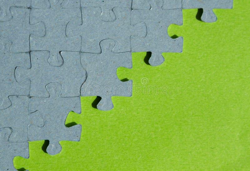 Fondo del pedazo del rompecabezas con el fondo verde fotos de archivo