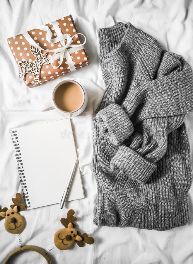 Fondo del planeamiento de la Navidad - taza de café, libreta limpia, caja de regalo, suéter hecho punto gris acogedor en la cama  fotografía de archivo