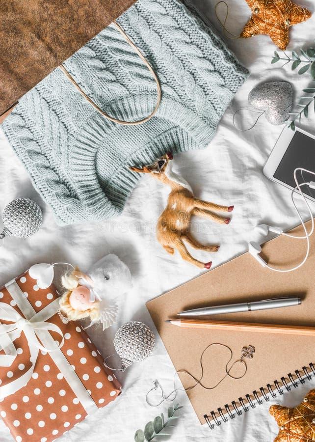 Fondo del planeamiento y de las compras de la Navidad El azul hizo punto el suéter en una bolsa de papel, libreta, teléfono, deco foto de archivo