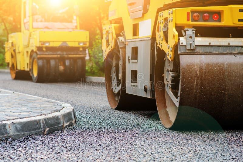 Fondo del rodillo del asfalto que apila y presiona el asfalto caliente Máquina de la reparación del camino imágenes de archivo libres de regalías