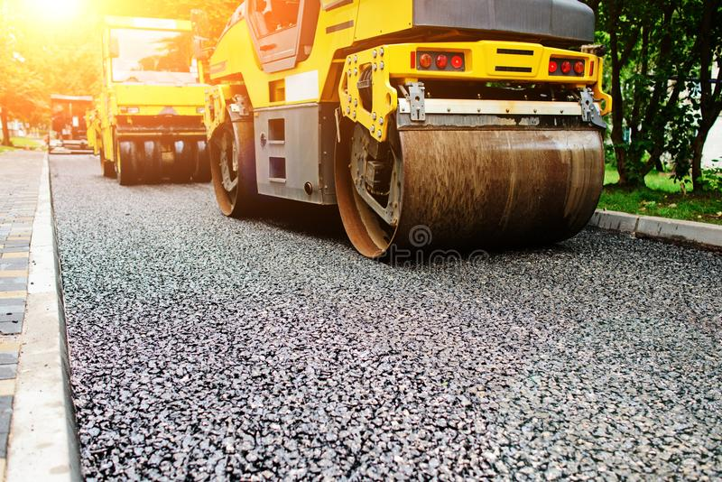 Fondo del rodillo del asfalto que apila y presiona el asfalto caliente Máquina de la reparación del camino fotos de archivo