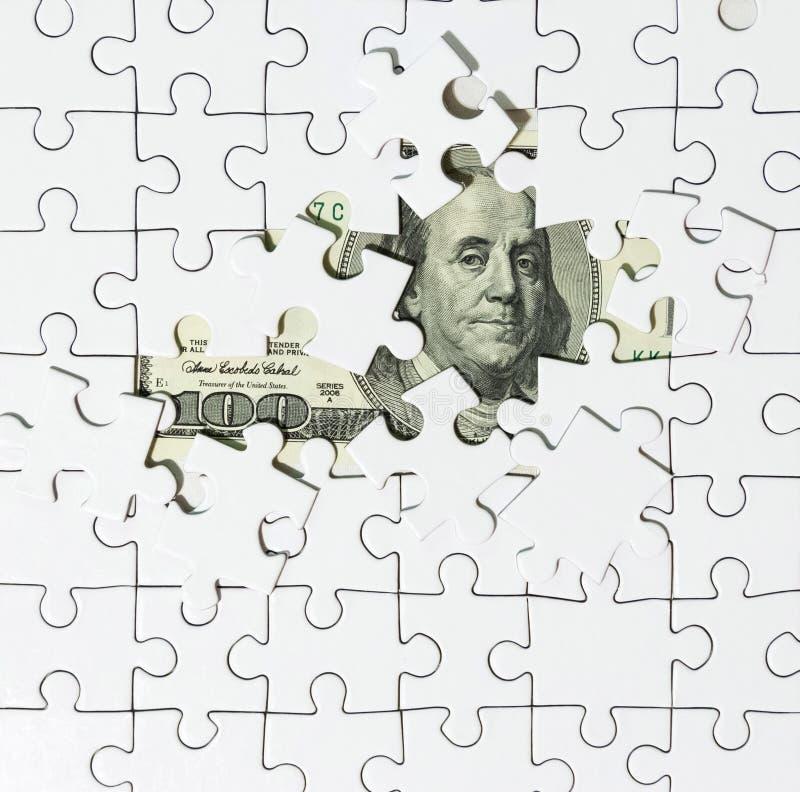 Fondo del rompecabezas blanco en el centro cuyo el billete de banco en 100 dólares imagenes de archivo
