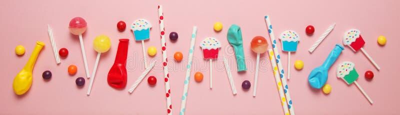 Fondo del rosa del cumplea?os de los ni?os Caramelos, bolas, velas y paja coloridos dispersados fotografía de archivo libre de regalías