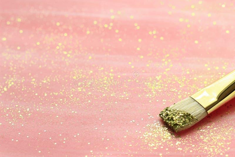 Fondo del rosa en colores pastel con brillo y el cepillo del oro imagenes de archivo