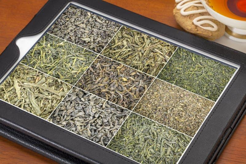 Fondo del té verde de las hojas intercambiables en la tableta fotografía de archivo