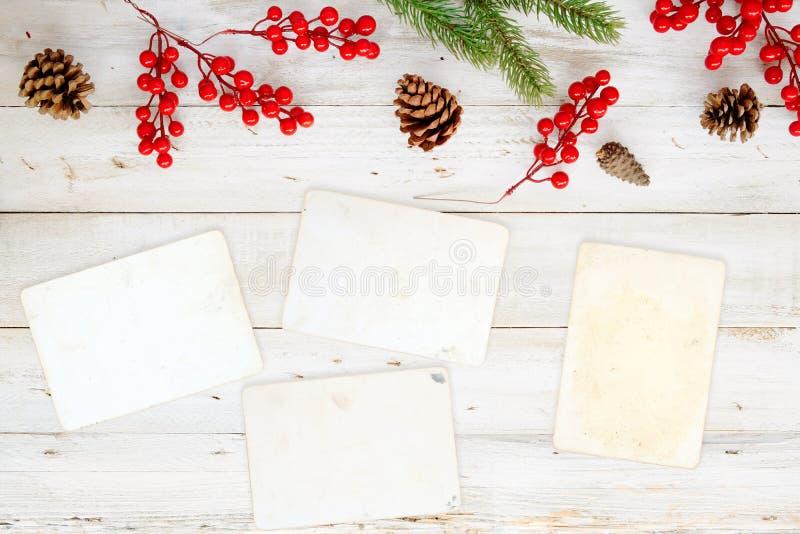 Fondo del tema de la Navidad con el papel en blanco de la foto y elementos del adornamiento en la tabla de madera blanca foto de archivo libre de regalías