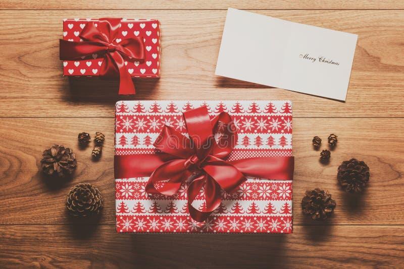 Fondo del tema de la Navidad, presente, conos del pino y tarjeta de Navidad mágicos en la tabla de madera imagen de archivo