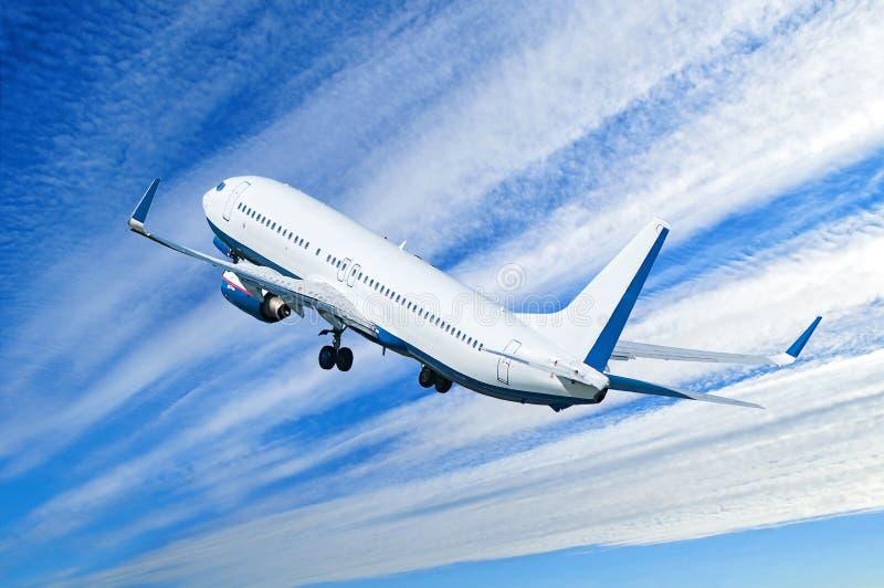 Fondo del viaje con el vuelo comercial blanco del aeroplano en el cielo dramático azul fotografía de archivo