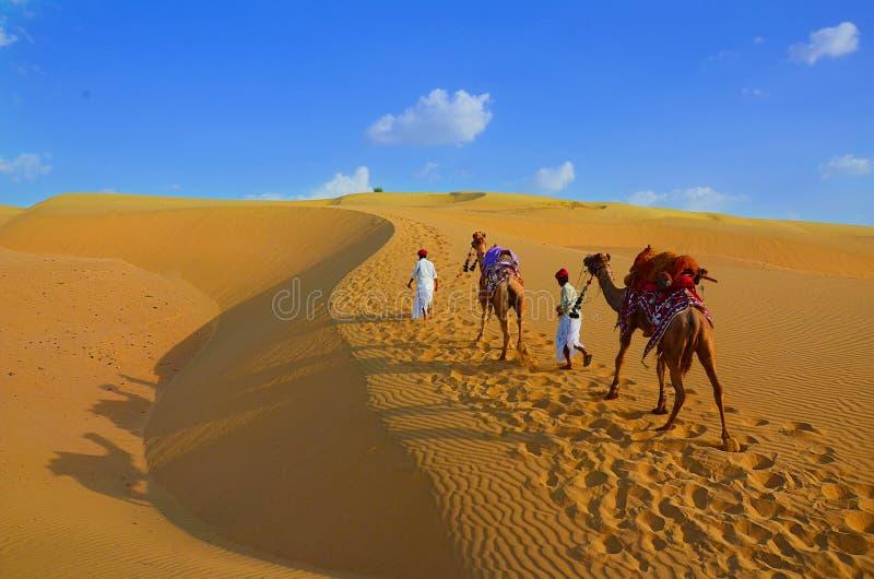 Fondo del viaje - dos cameleers con los camellos que caminan en las dunas de arena de oro del desierto de Thar contra el cielo az fotografía de archivo