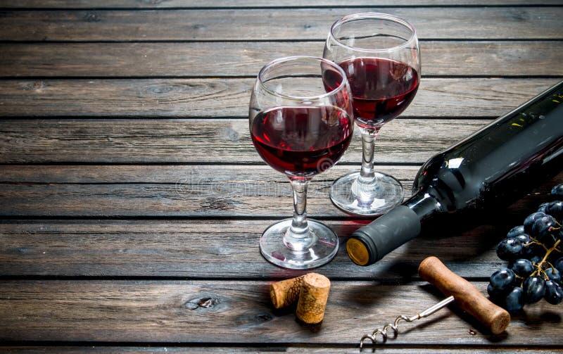 Fondo del vino Vino rojo en vidrios con las uvas imagen de archivo