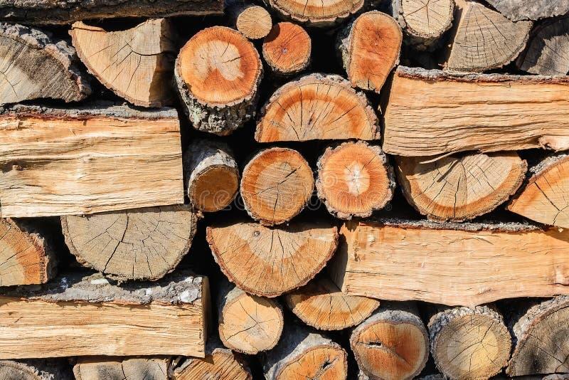 Fondo dell'estremità dei ceppi e dei firewoods asciutti Primo piano della pila all'aperto di legno un giorno soleggiato Legna da  immagini stock libere da diritti