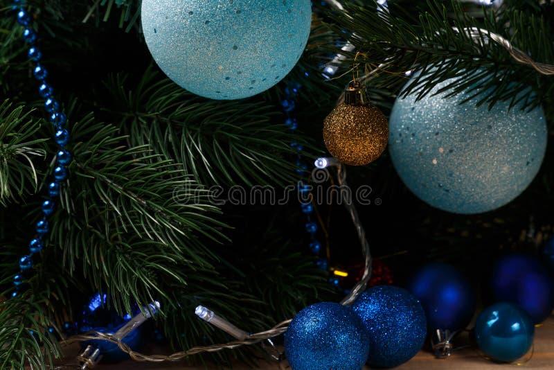 Fondo della decorazione del nuovo anno o di Natale: rami dell'pelliccia-albero, palle di vetro variopinte sul fondo nero di lerci fotografia stock libera da diritti