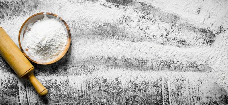 Fondo della farina Farina su un piatto con un matterello immagine stock libera da diritti