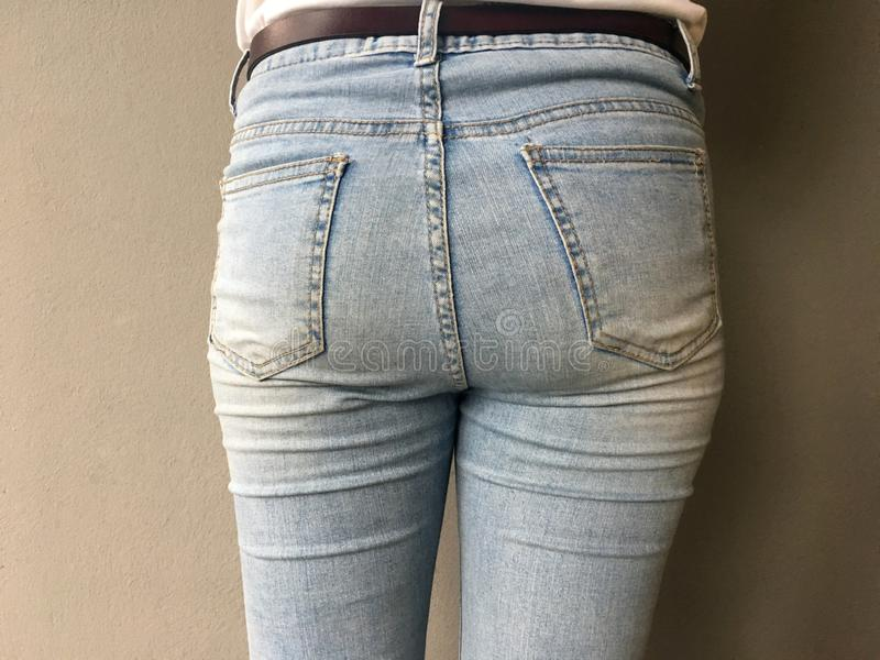 Fondo della giovane donna in blue jeans davanti al fondo grigio della parete del cemento fotografia stock libera da diritti