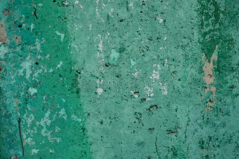 Fondo della parete misera strutturata verde con le macchie di pittura e dei fori nella luce del giorno Primo piano Copi lo spazio fotografie stock