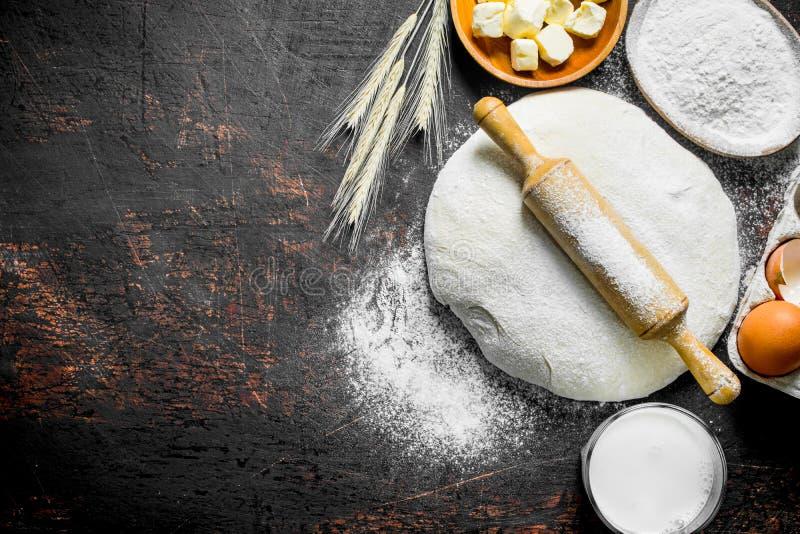 Fondo della pasta Pasta con burro, latte e farina in ciotole immagini stock