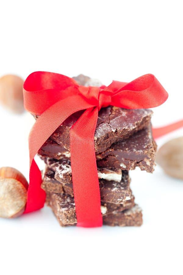 Pila di cioccolato con il nastro ed i dadi rossi fotografie stock libere da diritti