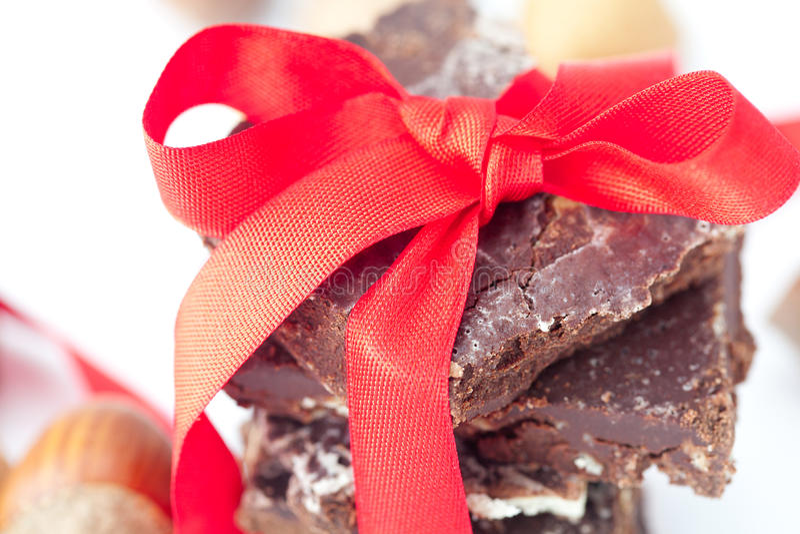 Pila di cioccolato con il nastro ed i dadi rossi fotografie stock