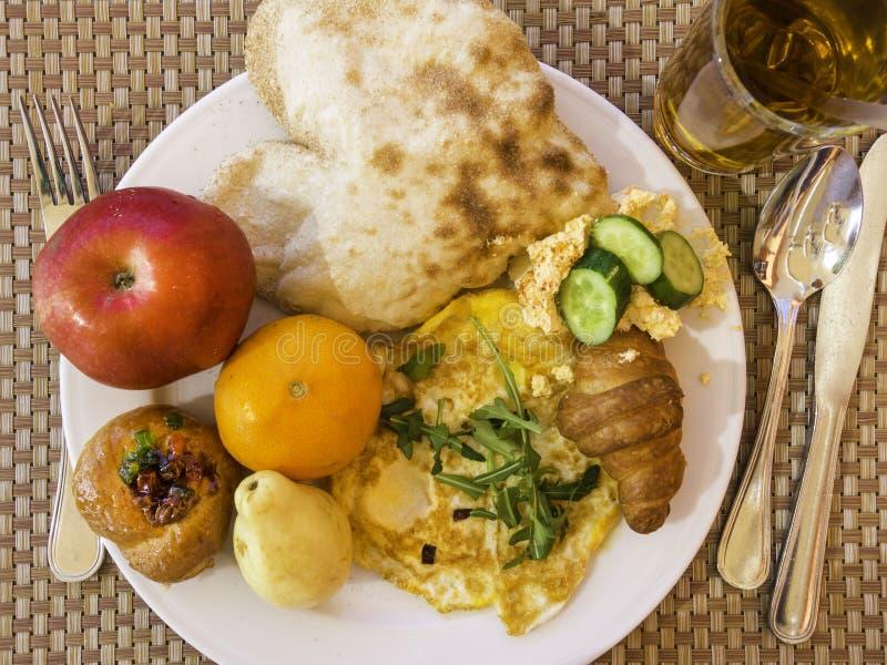 Fondo della prima colazione di salute, frutti, croissant, omlette, succo, pita con il hummus fotografia stock libera da diritti