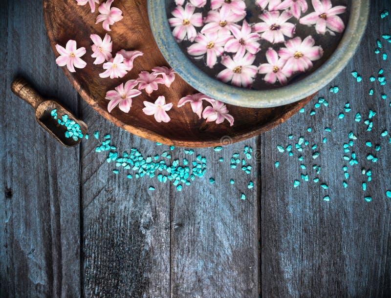 Fondo della stazione termale con sale marino, la ciotola, i fiori ed acqua, immagine stock libera da diritti