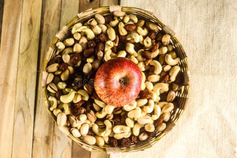 Fondo della stuoia e di legno con frutta secca e la mela immagini stock