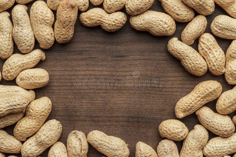 Fondo delle arachidi con sulla tavola di legno fotografia stock