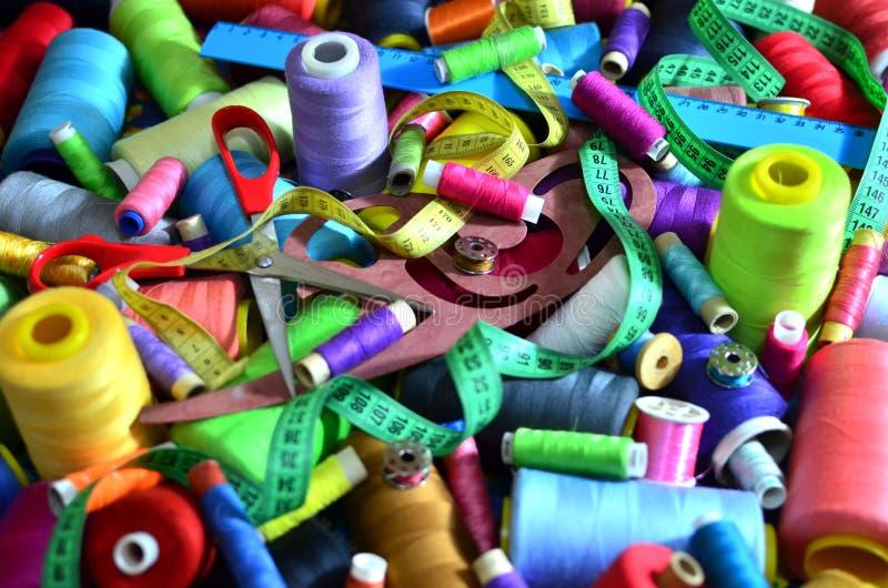 Fondo delle bobine con i fili multicolori per cucire Cucito, cucente ed adattante concetto immagini stock